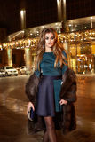 Beautiful young sexy blonde wearing evening makeup in elegant fitting dress fashionable stylish expensive fur coat walk night stre Royalty Free Stock Photo