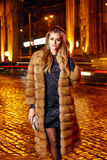Beautiful young sexy blonde wearing evening makeup in elegant fitting dress fashionable stylish expensive fur coat walk night stre Royalty Free Stock Photos
