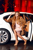 Beautiful young sexy blonde wearing evening makeup in elegant fitting dress fashionable stylish sitting in cabin of expensive car. Comes out of it in hand Stock Images