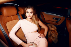 Beautiful young sexy blonde wearing evening makeup in elegant fitting dress fashionable stylish sitting in cabin of expensive car. Comes out of it in hand Stock Photography