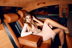 Beautiful young sexy blonde wearing evening makeup in elegant fitting dress fashionable stylish sitting in cabin of expensive car. Comes out of it in hand Royalty Free Stock Photo