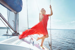 Beautiful young sexy brunette girl in a dress and makeup, summer trip on a yacht with white sails on the sea or ocean in the Gulf Royalty Free Stock Image