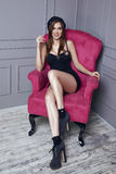 Beautiful young sexy brunette woman in black beret and a short silk dress smokes a cigarette sitting in pink armchair stylish clot. Hes trendy shoes fashion Stock Photos