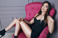 Beautiful young sexy brunette woman in black beret and a short silk dress smokes a cigarette sitting in pink armchair stylish clot Royalty Free Stock Photos