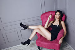 Beautiful young sexy brunette woman in black beret and a short silk dress smokes a cigarette sitting in pink armchair stylish clot Stock Photos