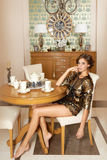 Beautiful young sexy brunette woman sitting in a restaurant on a chair at a table in a fancy restaurant dressed in shorts and a bl Stock Photo