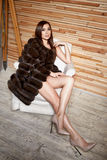 Beautiful young sexy brunette woman wearing a short dress stylish design and fashionable fur coat, beige heels shoes long thin leg Stock Image