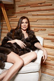 Beautiful young sexy brunette woman wearing a short dress stylish design and fashionable fur coat, beige heels shoes long thin leg Royalty Free Stock Image