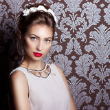 Beautiful young sexy elegant woman with red lips, beautiful stylish hairstyle with white flowers in her hair, the way Stock Photo