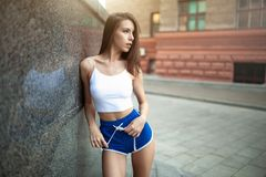 Beautiful young girl athlete resting after a hard athletic workout on a city street stock images
