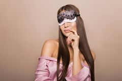 Beautiful young sexy girl in bathrobe with sleeping mask on beige background. Beautiful young sexy brunette girl in bathrobe with sleeping mask on beige Stock Image