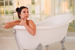 Beautiful young girl with dark hair in bathtub stock photo