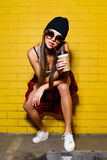 Beautiful young sexy girl drink coffee and sitting near yellow wall background in sunglasses, red plaid shirt, shorts. Beautiful young sexy hipster girl drink Royalty Free Stock Photo