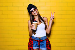 Beautiful young sexy girl drink coffee, smiling and posing near yellow wall background in sunglasses, red plaid shirt. Beautiful young sexy hipster girl drink Royalty Free Stock Photography