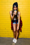 Beautiful young sexy girl drink coffee, smiling and posing near yellow wall background in sunglasses, red plaid shirt. Beautiful young sexy hipster girl drink Stock Photos