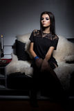 Beautiful young girl with full lips sitting on the sofa covered with white fur in a black little dress and stockings Stock Photo