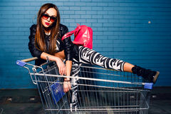 Beautiful young girl having fun sitting in shopping trolley cart near blue wall in sunglasses, pink backpack. Royalty Free Stock Photos