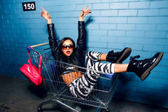 Beautiful young girl having fun sitting in shopping trolley cart near blue wall in sunglasses, pink backpack. Royalty Free Stock Images
