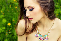 Beautiful young sexy girl with long hair and beautiful makeup with necklace on the neck sitting on the grass in the garden Royalty Free Stock Photo
