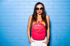 Beautiful young sexy girl posing and smiling near blue wall background in yellow swimsuit, sunglasses, pink backpack. Beautiful young sexy hipster girl posing Stock Photo