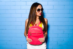 Beautiful young girl posing and smiling near blue wall background in yellow swimsuit, sunglasses, pink backpack. Royalty Free Stock Photos