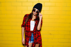 Beautiful young sexy girl posing and smiling near yellow wall background in sunglasses, red plaid shirt, shorts, hat. Beautiful young sexy hipster girl posing Royalty Free Stock Photo