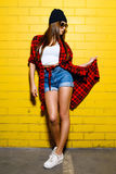 Beautiful young girl posing and smiling near yellow wall background in sunglasses, red plaid shirt, shorts. Royalty Free Stock Photos