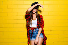 Beautiful young sexy girl posing and smiling near yellow wall background in sunglasses, red plaid shirt, shorts. Beautiful young sexy hipster girl posing and Royalty Free Stock Photo