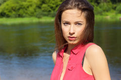 Beautiful young sexy girl in the red shirt is standing on the river Bank in Sunny day Stock Photography