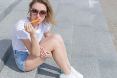 Beautiful young sexy girl sitting on the stairs in shorts and sunglasses and eating a delicious ice cream bright Stock Photo