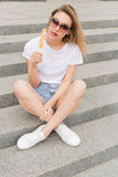 Beautiful young girl in sunglasses eating ice cream on the ladder and licking plump lips a bright sunny hot day Royalty Free Stock Images