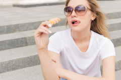 Beautiful young sexy girl in sunglasses eating ice cream on the ladder and licking plump lips a bright sunny hot day Royalty Free Stock Image