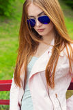 Beautiful young sexy girl in sunglasses walking on a bright sunny summer day on city streets Stock Photography
