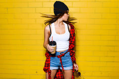 Beautiful young sexy hipster girl with flowing hair drink coffee, smiling and posing near urban yellow wall. Beautiful young sexy hipster girl with flowing hair Stock Images