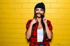 Beautiful young sexy hipster girl posing, smiling, do fake mustache near urban yellow wall background. Stock Photos