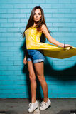 Beautiful young sexy hipster girl posing and smiling near urban blue wall background in yellow dress, shorts, shirt. Beautiful young sexy hipster girl posing Royalty Free Stock Images