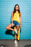 Beautiful young sexy hipster girl posing and smiling near urban blue wall background in yellow dress, shorts, shirt. Beautiful young sexy hipster girl posing Stock Photography