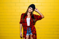 Beautiful young sexy hipster girl posing and smiling near urban yellow wall background in red plaid shirt, shorts, hat. Beautiful young sexy hipster girl posing Royalty Free Stock Images