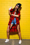 Beautiful young sexy hipster girl posing and smiling near urban yellow wall background in red plaid shirt, shorts, hat. Beautiful young sexy hipster girl posing Royalty Free Stock Photography