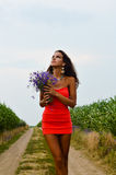 Beautiful young lady holding wildflowers and. Picture of beautiful young woman in mini coral dress walking on summer countryside road. Pretty girl holding royalty free stock photo