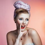 Beautiful young pin-up girl with surprised expression, on white background Royalty Free Stock Photography