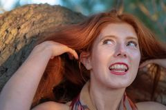 Beautiful young red-haired girl is smiling happily at a beautiful red hair. Beautiful young red-haired girl is smiling happily at a beautiful gorgeous red hair stock photos