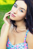 Beautiful young sexy sweet girl with blue eyes with long black hair sitting in the Park on a clear summer day Royalty Free Stock Photo