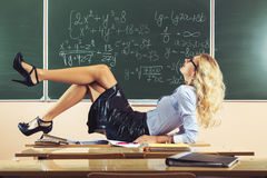 Beautiful young sexy teacher. Posing on table Royalty Free Stock Photo