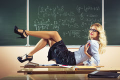 Beautiful young sexy teacher. Posing on table Royalty Free Stock Photos
