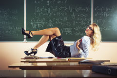 Beautiful young teacher. Posing on table stock photography