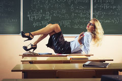 Beautiful young sexy teacher. Posing on table Stock Images