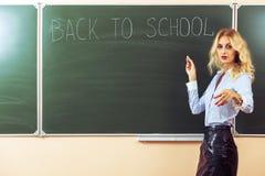 Beautiful young sexy teacher. Standing near the blackboard Stock Photo