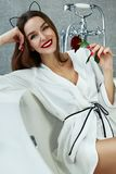 Woman in bathroom in silk robe rose Valentine`s day. Beautiful young woman with dark hair, evening make-up, red lips and manicure sitting in the bathroom in a stock image
