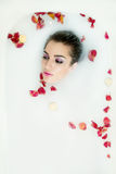 Beautiful young sexy woman with dark hair wet and makeup in milk. Bath. Wellness  and SPA in beauty cosmetic salon and spa.  Bath water procedures for perfect Stock Image